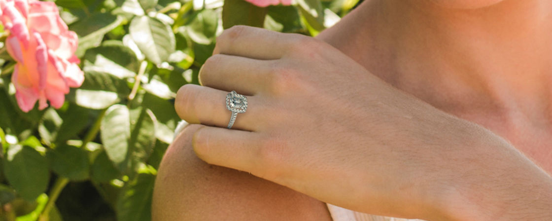 woman's hand on shoulder wearing emerald cut halo engagement ring