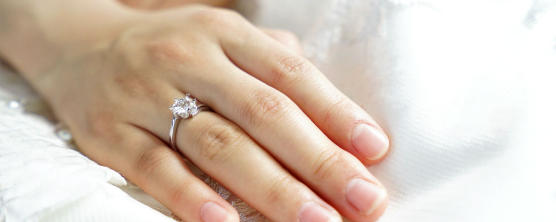 woman's hand on white wearing floating diamond engagement ring
