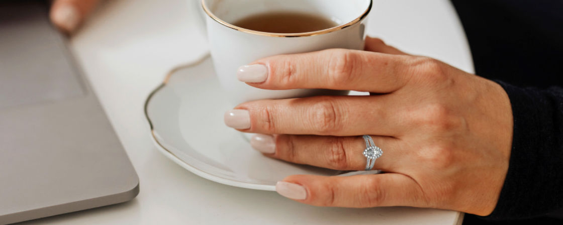 woman holding tea cup wearing marquise halo engagement ring