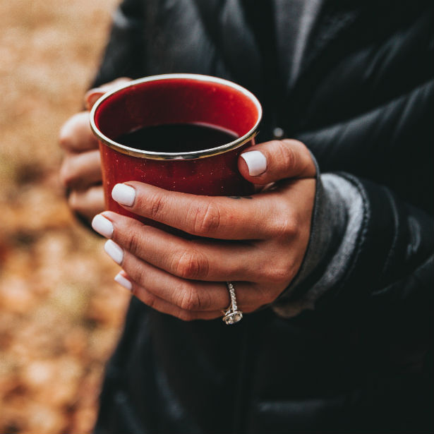 woman's hands holding coffee cup wearing trellis engagement ring