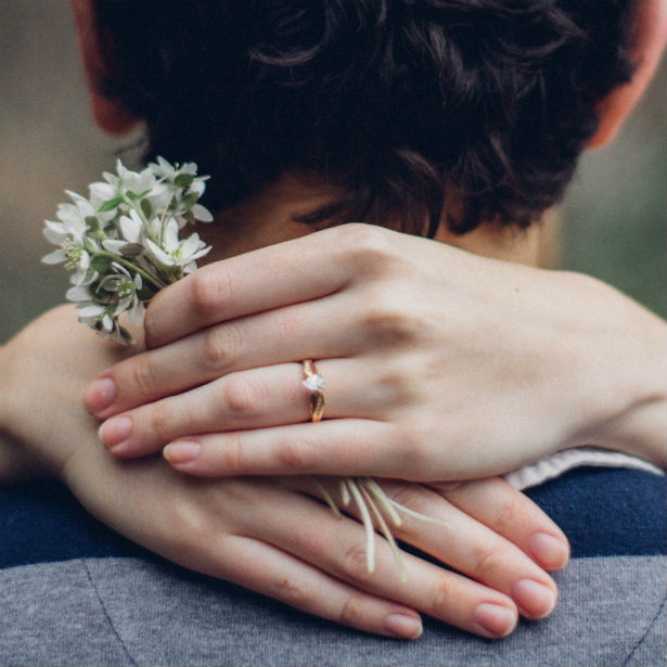 woman's hands wrapped around fiance wearing rose gold pear shaped engagement ring