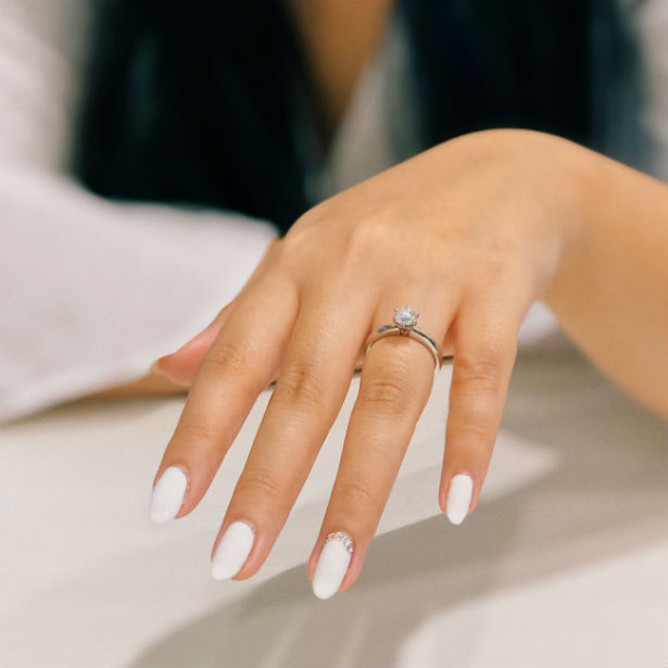 woman's outstretched hand wearing engagement ring