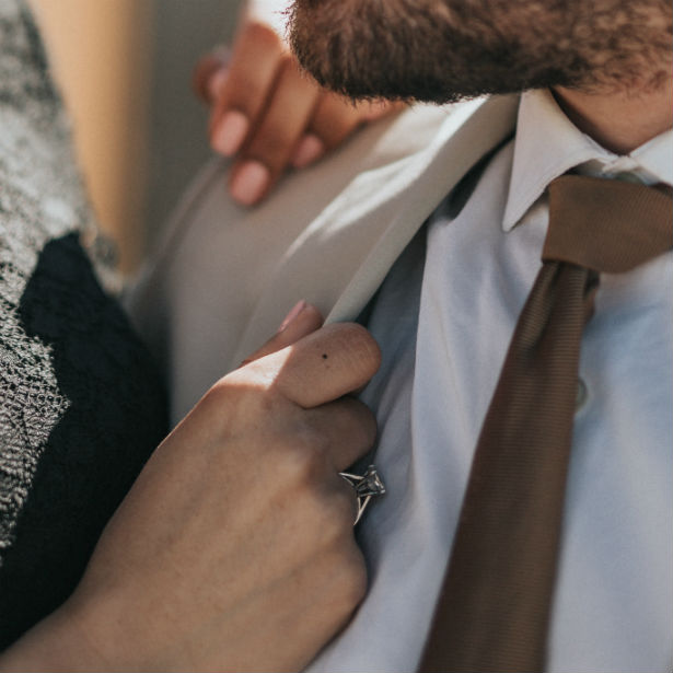 woman wearing high setting engagement ring with hand on fiance's chest