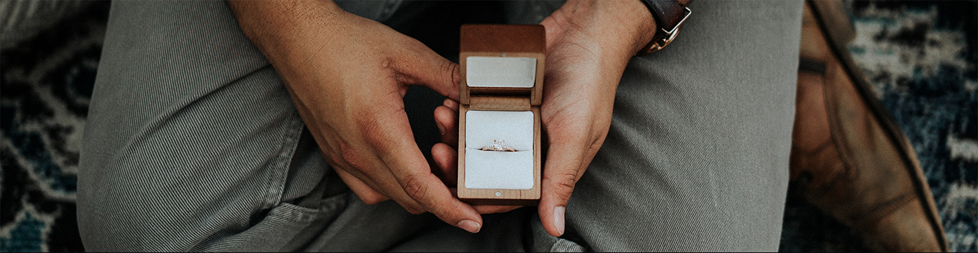 Man holding engagement ring box for a proposal