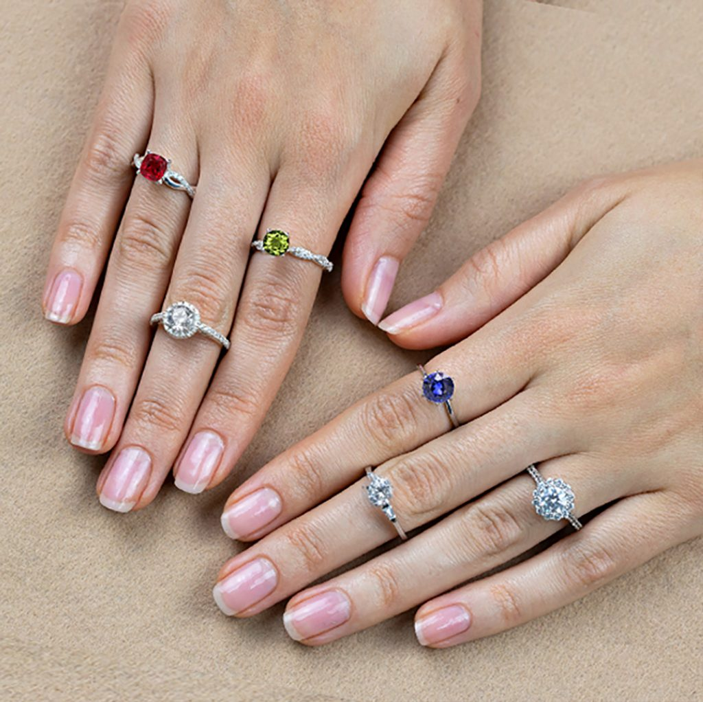Gemstone rings on hand: Ruby, Moissanite, Peridot, Blue Sapphire, Diamond