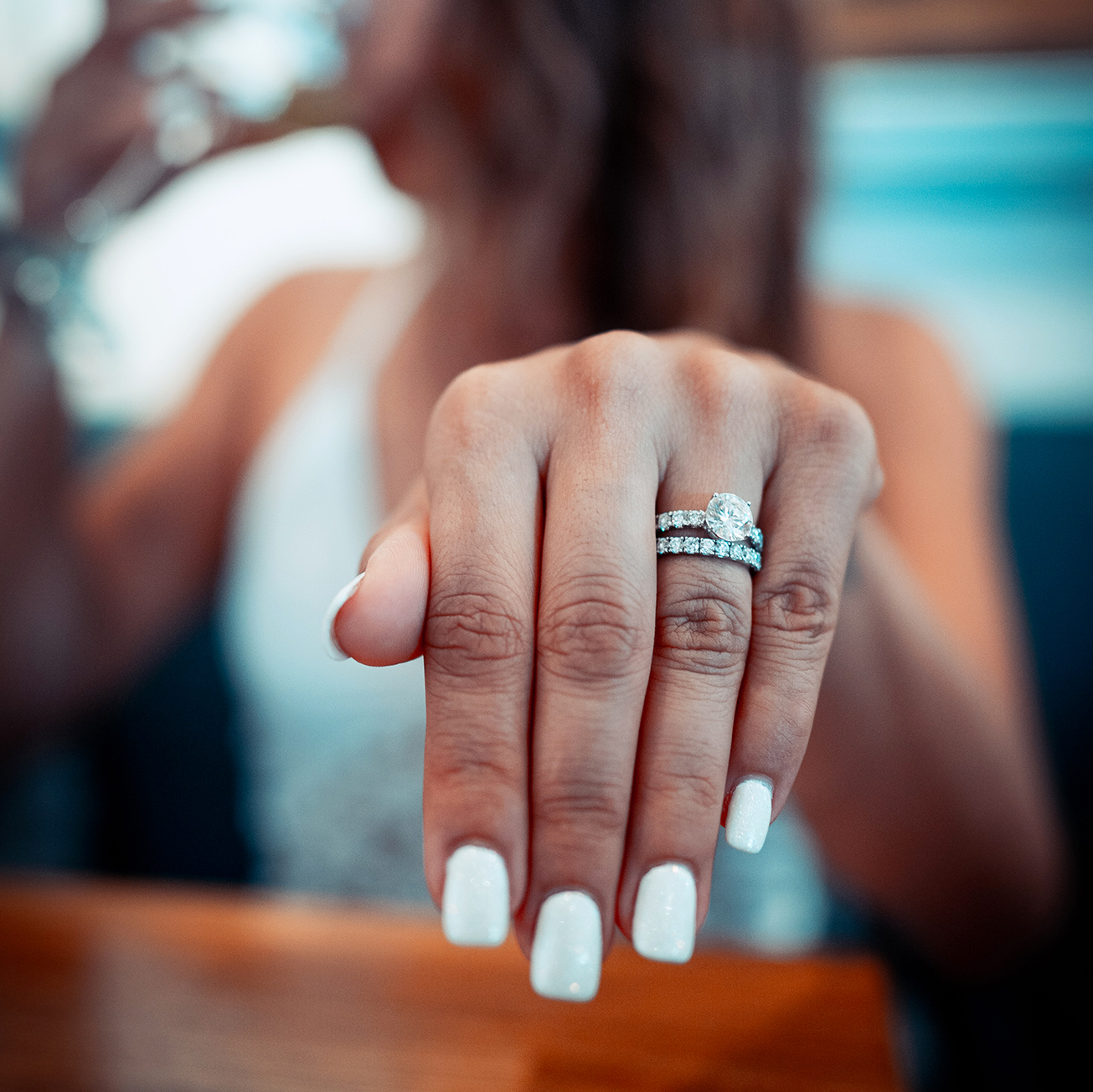 Woman wearing white gold engagement ring and wedding ring