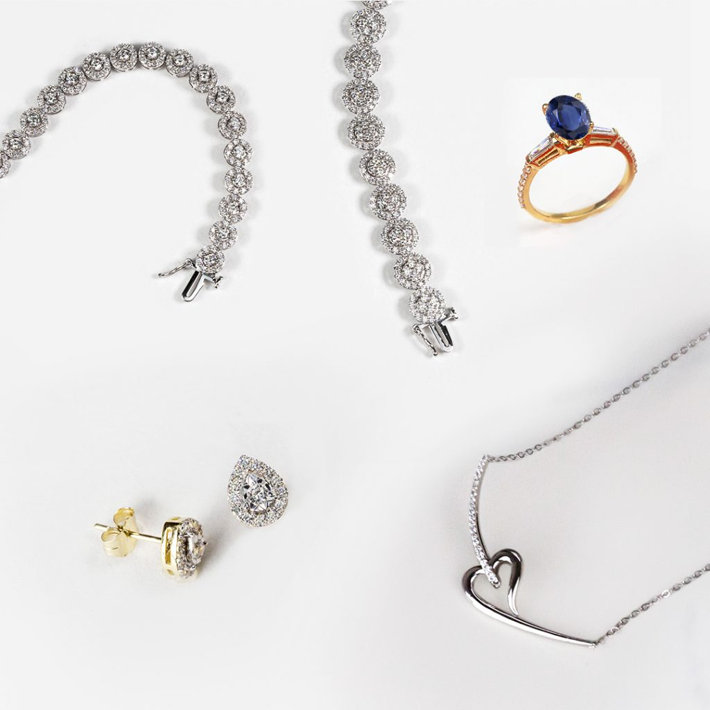 Wedding day jewelry: diamond bracelet, pear lab diamond halo stud earrings, blue sapphire ring, and heart necklace