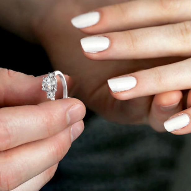 man sliding three stone engagement ring on woman's finger