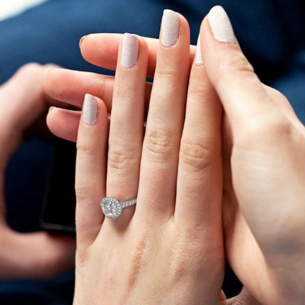 cushion cut halo engagement ring on woman's finger
