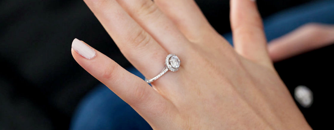 round halo engagement rings woman's hand