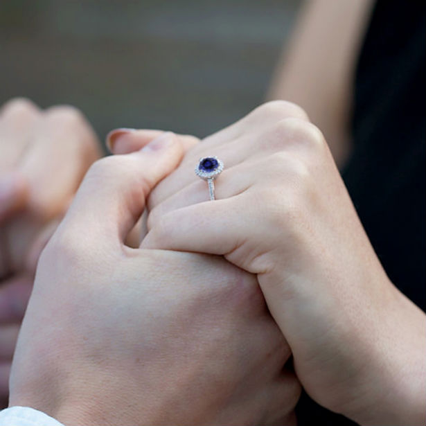 sapphire and diamond engagement rings couple's hands