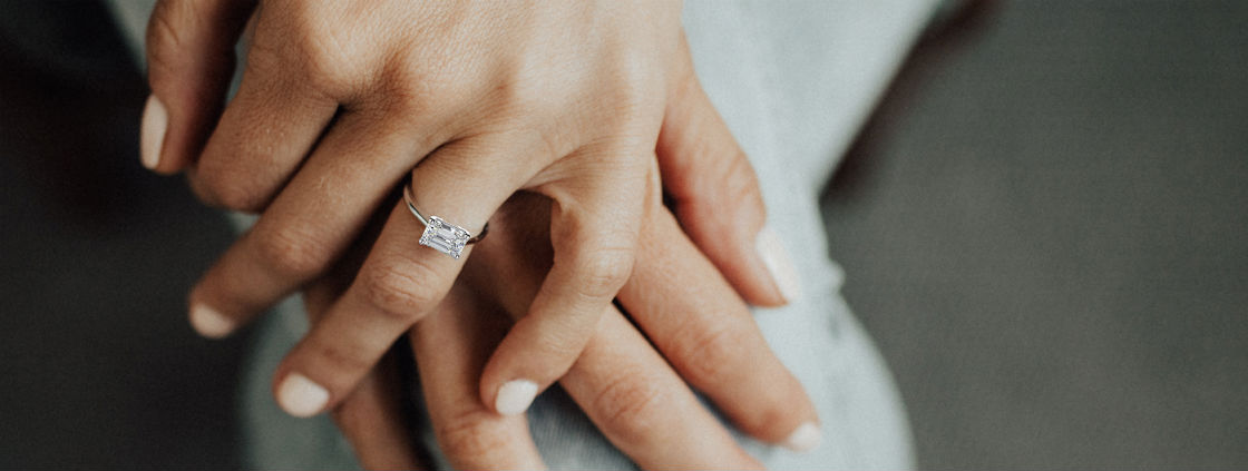 east west engagement rings woman's hands