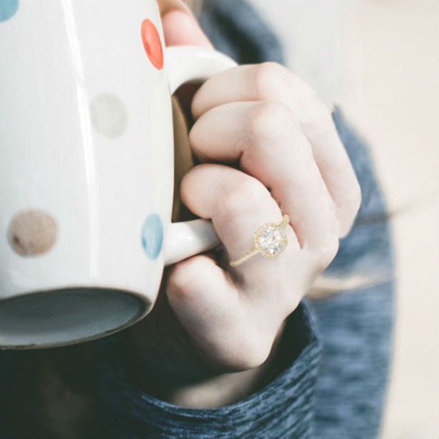 woman holding mug wearing yellow gold cushion cut engagement ring