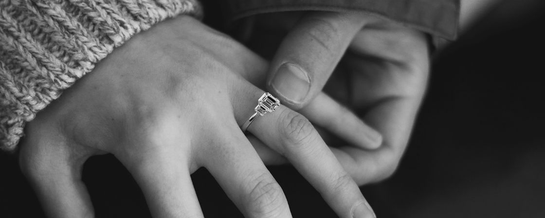 womans hand wearing emerald cut three stone engagement ring