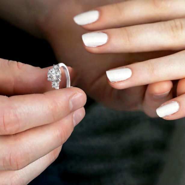 man putting oval three stone engagement ring on woman's finger