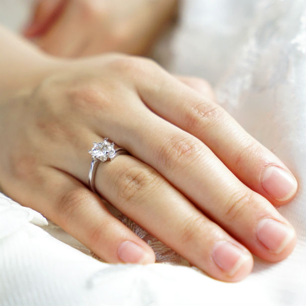 woman's hand wearing floating diamond engagement ring