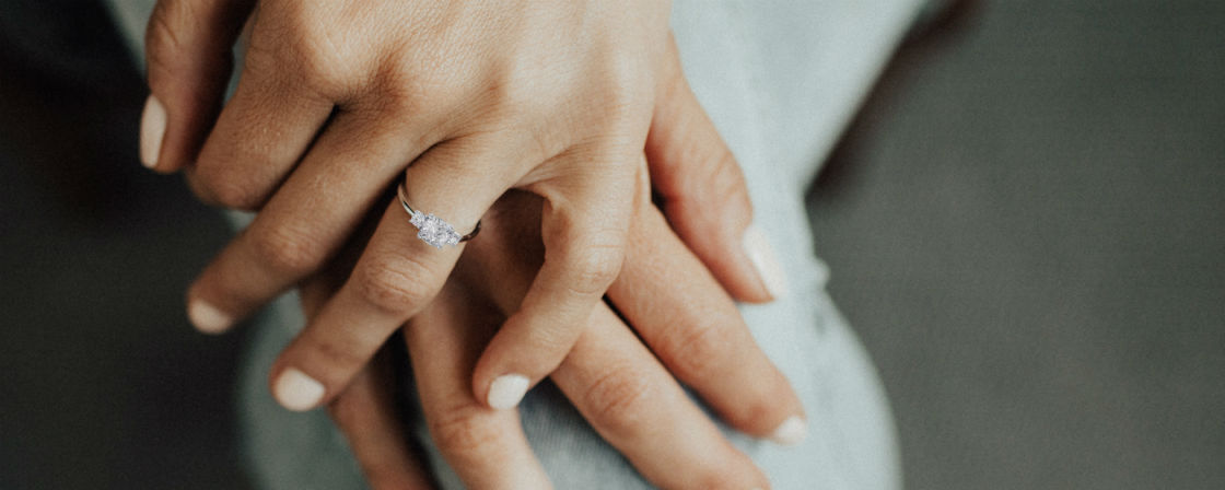 woman's crossed hands wearing cushion cut three stone engagement ring