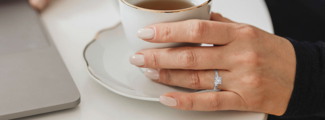 woman holding cup wearing princess cut three stone engagement ring