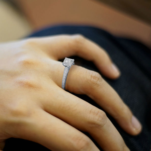 womans hand wearing a cathedral engagement ring
