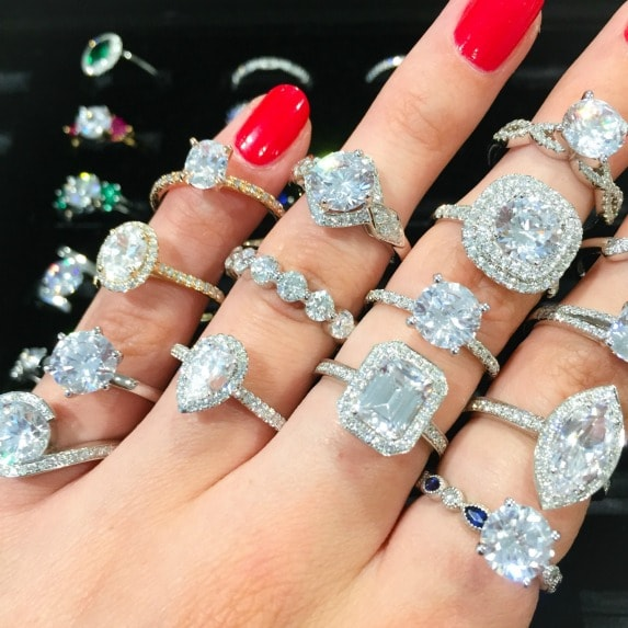 hand with many diamond  engagement ring styles on it