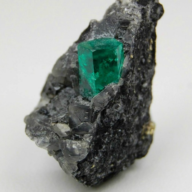 a rough uncut emerald rowing naturally in a rock formation