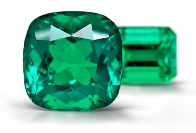 sparkling natural cushion emerald showing light performance and brilliance with another emerald shaped green emerald behind it