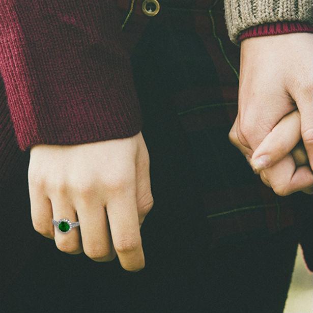woman wearing emerald and diamond engagement ring holding husbands hand