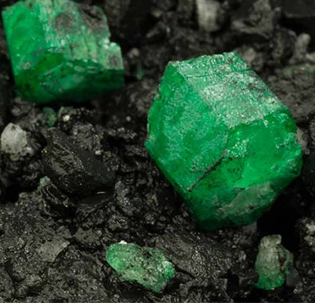 emerald attached to rock in a natural environment as it is mined from the earth