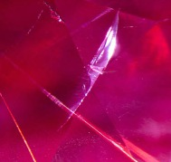 natural cracks like feathers growing in the ruby and breaking the surface