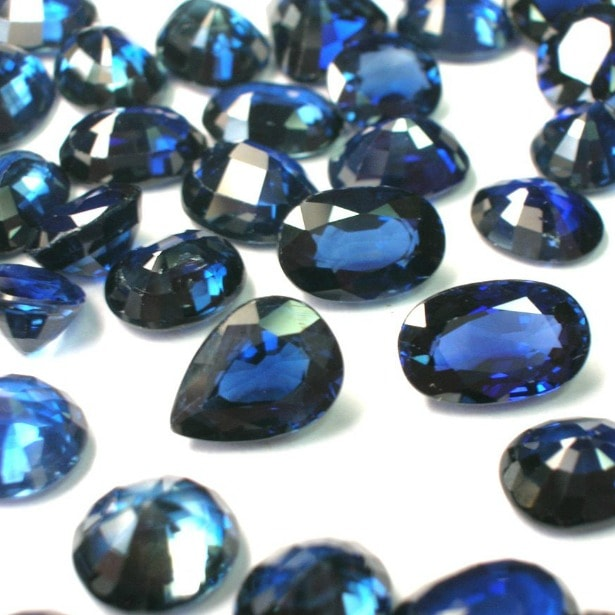 loose blue sapphires in many shapes, pear, round, oval on a white surface