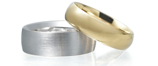 a 14kt yellow gold ring contrasting a 14kt white gold ring for color comparison