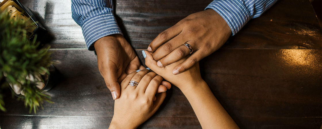 couple holding hands wearing white gold or platinum rings